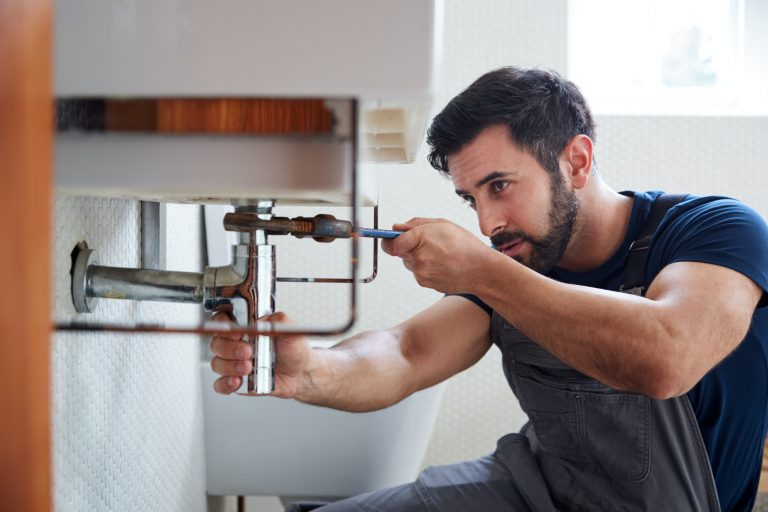 Male Plumber Using Wrench To Fix Leaking Sink In Home Bathroom