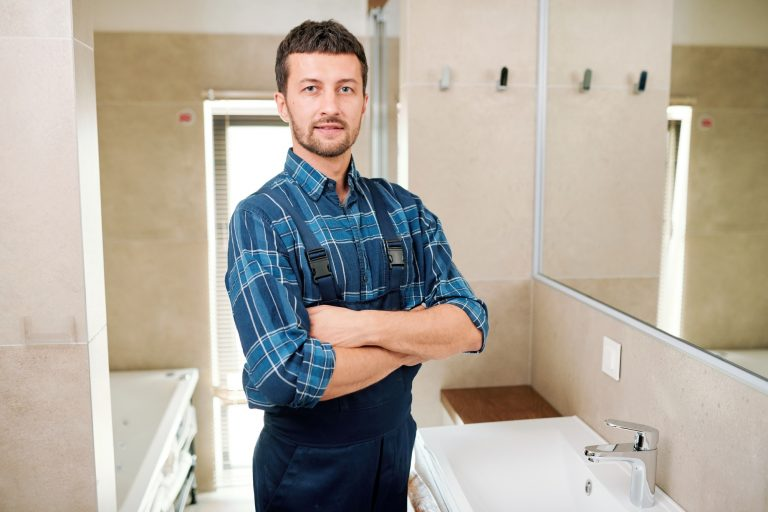 Young successful plumber in workwear standing in bathroom